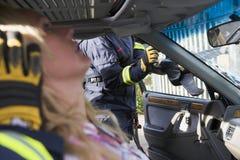Sapeurs-pompiers aidant une femme blessée dans un véhicule photos stock