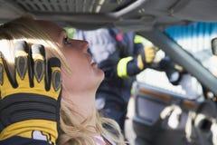 Sapeurs-pompiers aidant une femme blessée dans un véhicule image libre de droits