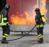 Sapeurs-pompiers avec des bouteilles d'oxygène outre du feu photographie stock
