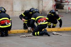 Sapeurs-pompiers avec l'échelle pour atteindre les planchers supérieurs de la construction photo libre de droits