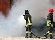 sapeurs-pompiers avec l'uniforme et le casque protecteurs outre du feu images stock