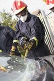 Sapeurs-pompiers cassant un pare-brise de véhicule images stock