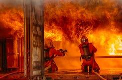 Sapeurs-pompiers combattant un feu, formation de sapeur-pompier photos stock