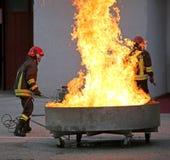 Sapeurs-pompiers courageux pendant l'essai d'un extincteur photo libre de droits