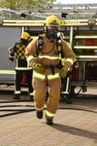 Sapeurs-pompiers dans des appareils respiratoires sur le mouvement Images stock