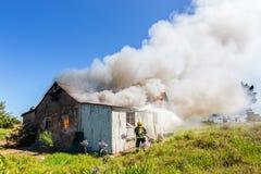 sapeurs-pompiers dans l'action enregistrant une maison brûlante Photo libre de droits