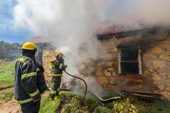 Sapeurs-pompiers dans l'action pendant une légende de secours pour une maison brûlante Photos stock