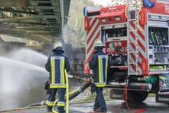Sapeurs-pompiers dans l'uniforme pendant la formation photo stock