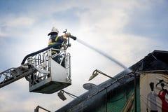Sapeurs-pompiers dans le combat d'action, s'éteignant le feu, dans la fumée Photos libres de droits