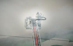 Sapeurs-pompiers dans le combat d'action, s'éteignant le feu, dans la fumée Images libres de droits