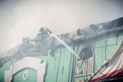 Sapeurs-pompiers dans le combat d'action, s'éteignant le feu, dans la fumée Photos stock