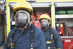 Sapeurs-pompiers dans les vêtements de travail protecteurs photo stock