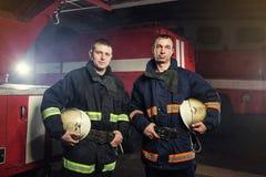 Sapeurs-pompiers de pompier dans l'action se tenant près d'un firetruck Eme photo libre de droits