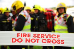 Sapeurs-pompiers derrière le cordon à un feu Photo stock