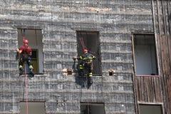 sapeurs-pompiers escaladant un mur d'une maison pendant l'exercice contre l'incendie photos libres de droits