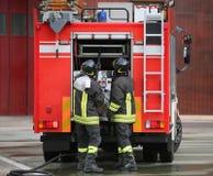 Sapeurs-pompiers et le camion de pompiers pendant une mission images libres de droits