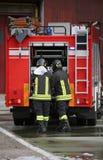 Sapeurs-pompiers et le camion de pompiers pendant une mission photographie stock libre de droits