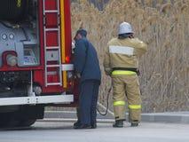 Sapeurs-pompiers et un camion de pompiers près de la route photographie stock