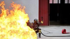 Sapeurs-pompiers pendant l'exercice pour le caus extincteur images libres de droits