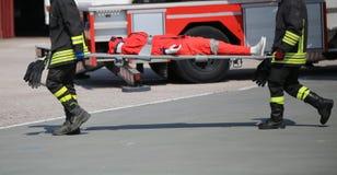 Sapeurs-pompiers pendant l'exercice pour porter blessé avec le s photo libre de droits