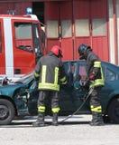 Sapeurs-pompiers pendant la délivrance après l'accident de la circulation Image stock