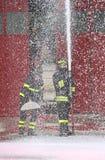 sapeurs-pompiers pendant un exercice dans la caserne de pompiers et la mousse photographie stock libre de droits