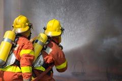 2 sapeurs-pompiers pulvérisant l'eau dans l'opération de lutte contre l'incendie Image stock