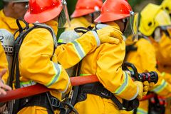 Sapeurs-pompiers pulv?risant l'eau ? haute pression pour mettre le feu avec l'espace de copie, grand feu dans la formation, sapeu images stock