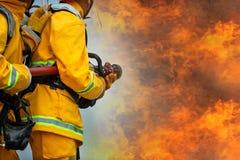 Sapeurs-pompiers pulv?risant l'eau ? haute pression pour mettre le feu avec l'espace de copie, grand feu dans la formation, sapeu photographie stock libre de droits