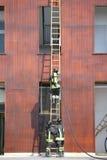sapeurs-pompiers sur l'échelle en bois pendant la lutte contre l'incendie dans le sapin image stock