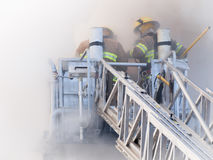 Sapeurs-pompiers sur la plate-forme dans la fumée lourde photos libres de droits