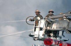 Sapeurs-pompiers sur un camion de pompiers d'unité de tour photo stock