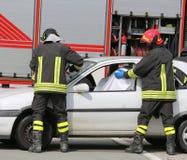 Sapeurs-pompiers tout en enregistrant le blessé dans la voiture endommagée photos libres de droits