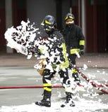 Sapeurs-pompiers tout en s'éteignant le feu avec la mousse image stock