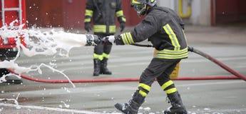Sapeurs-pompiers tout en s'éteignant le feu avec la mousse photos libres de droits