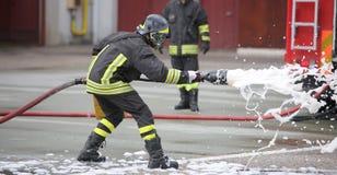 Sapeurs-pompiers tout en s'éteignant le feu avec la mousse photographie stock libre de droits