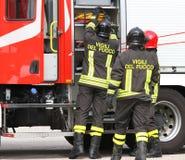 Sapeurs-pompiers travaillant près du camion de pompiers en manipulant une émergence images libres de droits