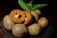 Sapodilla fruit with green leaves isolated on wooden background stock photo