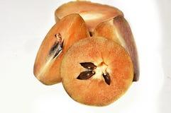 Sapodillafrukt med gr?na sidor som isoleras p? vit bakgrund arkivbild