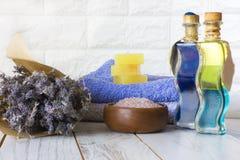 Sapone e sale da bagno naturale della lavanda, petrolio francese ed asciugamani su un fondo di legno bianco fotografie stock libere da diritti