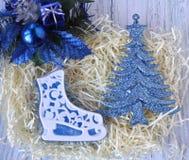 Sapone fatto a mano sotto forma dei pattini da ghiaccio e delle decorazioni blu di Natale su un fondo leggero fotografia stock