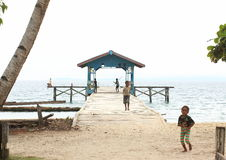 Saporkren Village. Jetty to the sea with kids playing around. Saporkren Village, a remote coastal area in Waigeo Island, Raja Ampat, West Papua Royalty Free Stock Photos