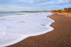 Sparkling surf at seashore landscape by sunrise Stock Images
