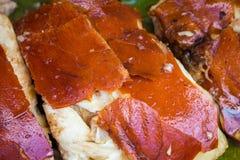 Sappig die varkensvleesvlees bij de grill wordt gekookt Gesneden varkensvleesbarbecue met gouden huid stock foto's