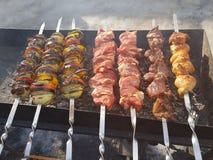 Sappig gemarineerd in de kebab van het kruidenvlees op vleespennen, gekookt en gebraden op een brand en een houtskool roostert gr stock foto's