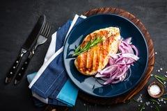 Sappig geroosterd kippenvlees, filet met verse gemarineerde ui op plaat Zwarte achtergrond, hoogste mening, close-up royalty-vrije stock fotografie