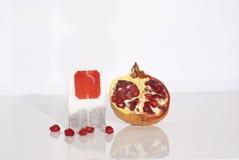 Sappig granaatappel en theezakje Stock Foto's