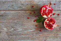 Sappig granaatappelfruit over houten uitstekende lijst Stock Foto