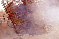 Sappig lapje vlees met kruiden bij bbq de grill in rook van brand Picknick in aard openlucht Stock Foto's