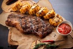 Sappig lapje vlees op de grill met rozemarijn, knoflook, Spaanse peper en graan op de grill en brood op de houten raad royalty-vrije stock afbeeldingen